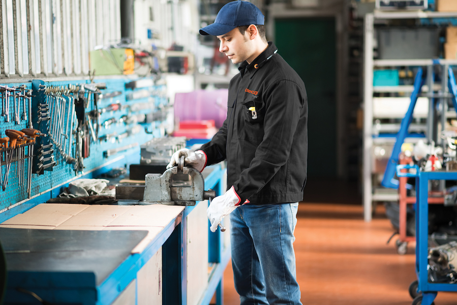 cleco care employee examines tools at work bench